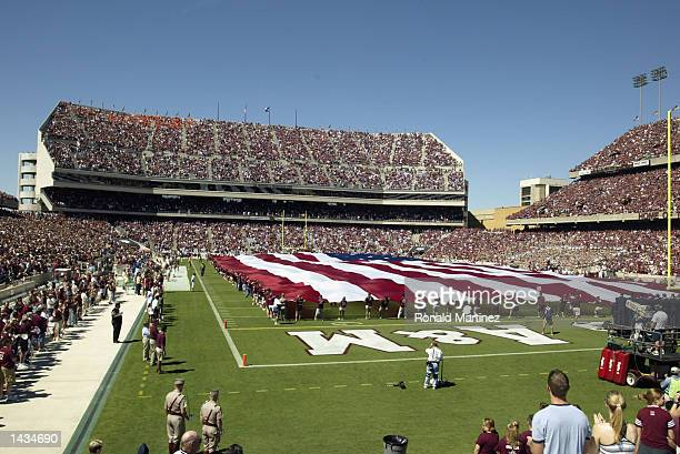 A giant American flag covers the field before the NCAA football game between the Virginia Tech Hokies and the Texas AM Aggies on September 21 2002 at...