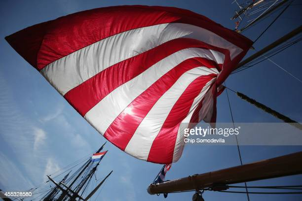 A giant American flag curls in the wind on the US Coast Guard Cutter Eagle where it is docked in the Inner Harbor as part of the Star Spangled...