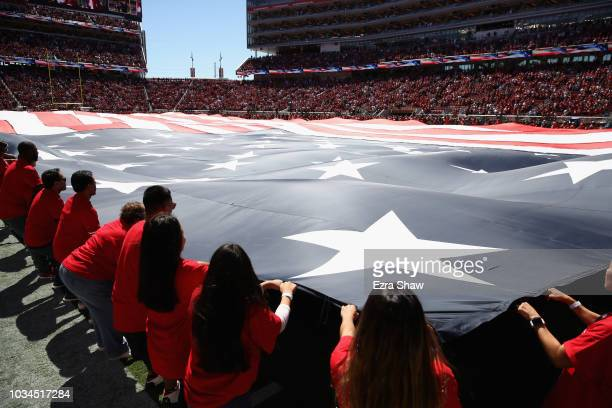 A giant American Flag is displayed during the National Anthem before the Detroit Lions game against the San Francisco 49ers at Levi's Stadium on...