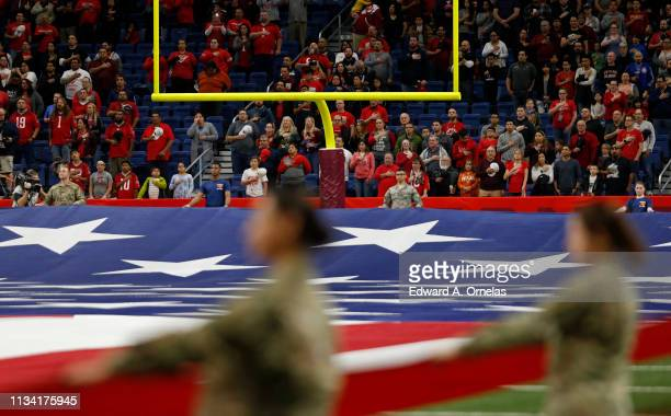 A giant American flag is held on the field during the national anthem before an Alliance of American Football game between the San Antonio Commanders...