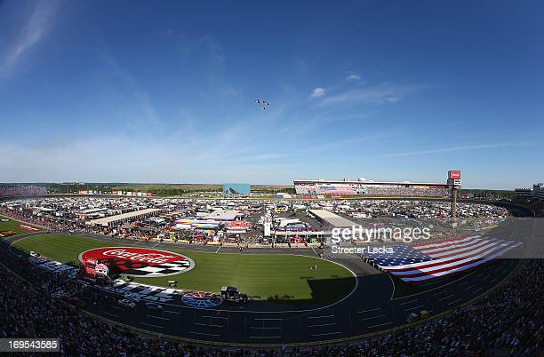 A giant American flag is help by members of the military during the national anthem prior to the NASCAR Sprint Cup Series CocaCola 600 at Charlotte...