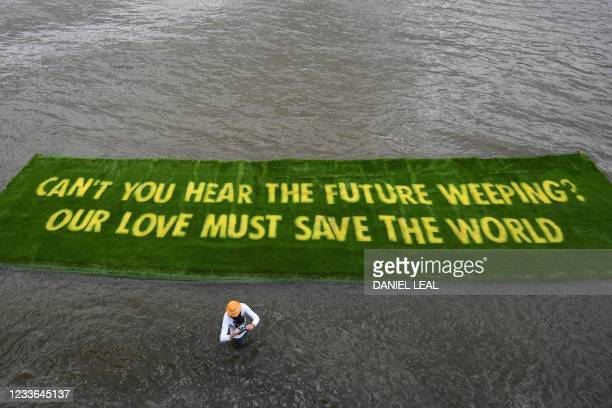 Giant banner declaring an environmental message, which is grown on a carpet of living grass and tells governments to Act Now in the lead-up to COP26,...