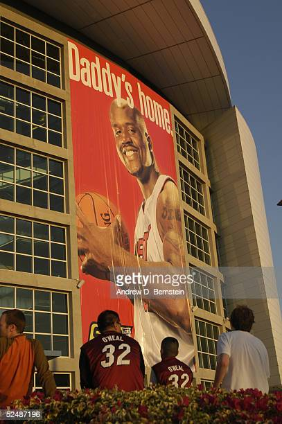 A giant banner of Shaquille O'Neal of the Miami Heat hangs outside American Airlines Arena as two fans look on wearing his uniform before the game...