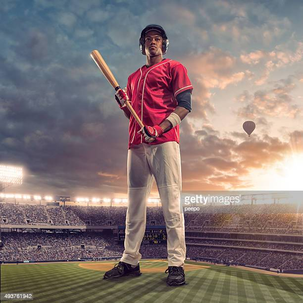 giant baseball batter standing in floodlit soccer stadium at sunset - baseball player stock pictures, royalty-free photos & images