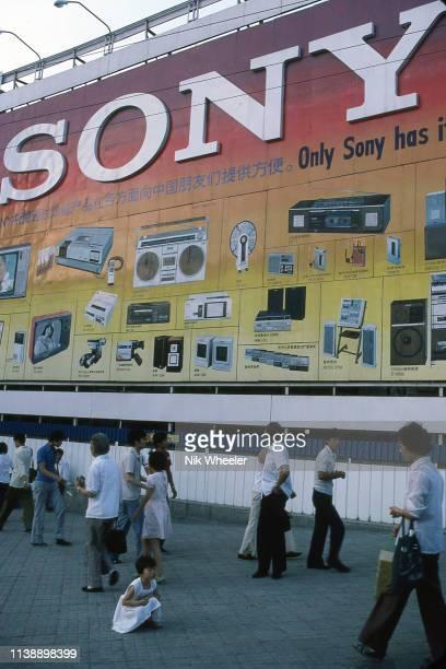 Giant billboard advertising Sony electronic products dwarfs pedestrians on Beijing city street circa 1984;m