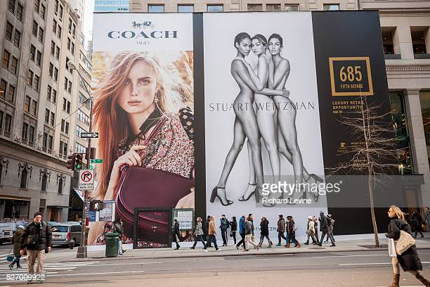 Giant billboards for Coach and its shoe brand Stuart Weitzman adorn the construction shed for the new 'Coach House' on Fifth Avenue in New York on...