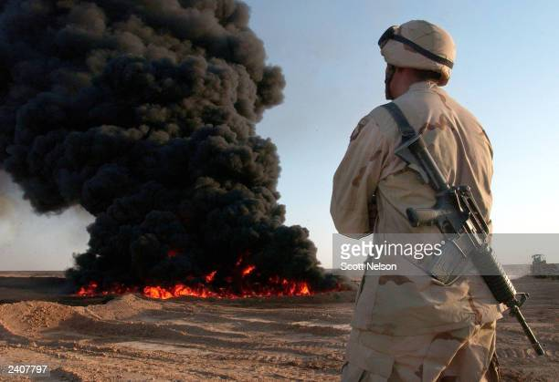 A giant black cloud of burning oil rises behind US Army 101st Airborne First Brigade Combat Team 426th Infantry Private First Class Michael Sheret...