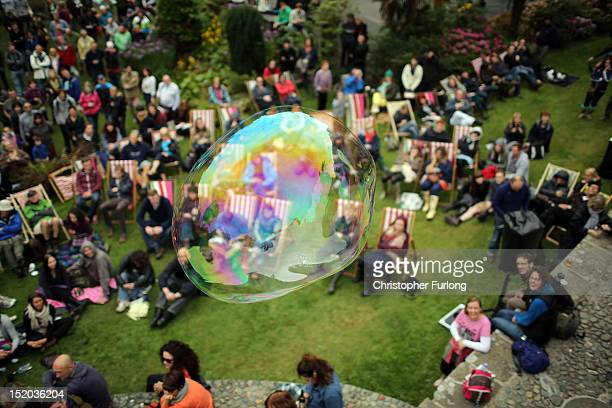Giant bubbles float amongst visitors as they enjoy the entertainment amongst the classical architecture of Portmeirion during the Number Six Festival...