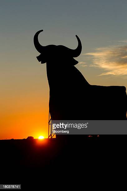 A giant bull advertisement for the Bodegas Osborne SA winery stands on display as the sun sets by a roadside near the company's vineyards in Malpica...
