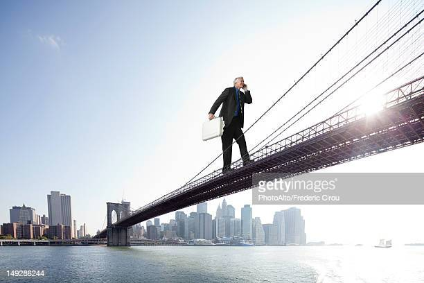 Giant businessman carrying briefcase stuffed with money across bridge