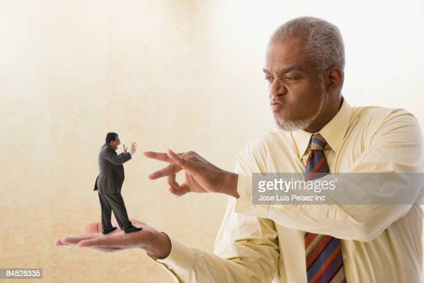 Giant businessman flicking miniature businessman