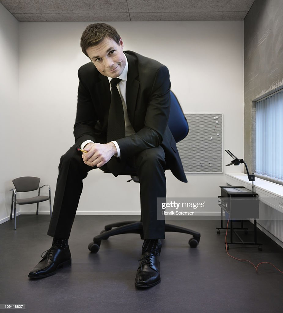 Giant businessman sitting on large chair in office : Stock Photo
