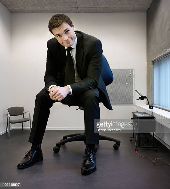 Giant businessman sitting on large chair in office