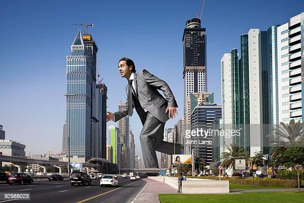 Giant businessman walking through skyscrapers