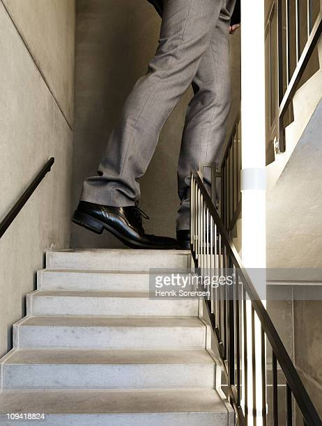 Giant businessman walking up staircase