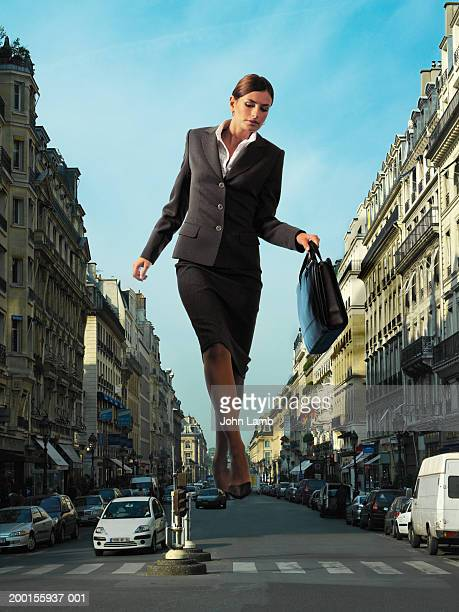 giant businesswoman walking in middle of city road (digital composite) - tamanho desproporcionado - fotografias e filmes do acervo