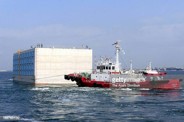A giant caisson is towed by tugboats at IHI's Aichi factory on May 15 2013 in Chita Japan The Caisson 50meterlong 203meterwidth and 195meterheight...