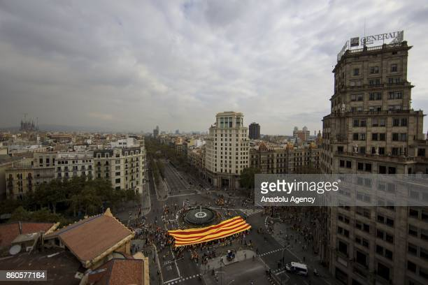 A giant Catalonian flag is carried by demonstrators during a demonstration supporting Spain unity on October 12 2017 in Barcelona Spain Spain...
