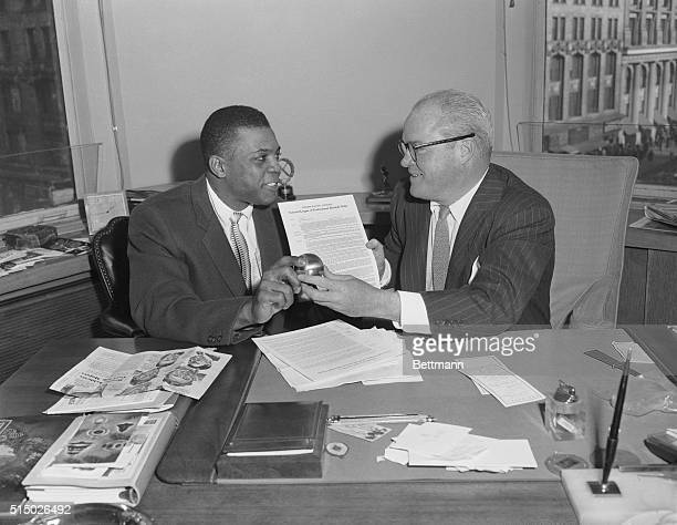 Giant centerfielder Willie Mays presents a belated Christmas gift a baseballenclosed watch to boss Horace Stoneham here after signing his 1957...