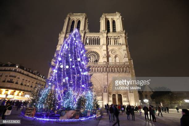 A giant Christmas tree is lit on the Parvis NotreDame in front of the NotreDame Cathedral in Paris on December 2 the first Christmas tree installed...