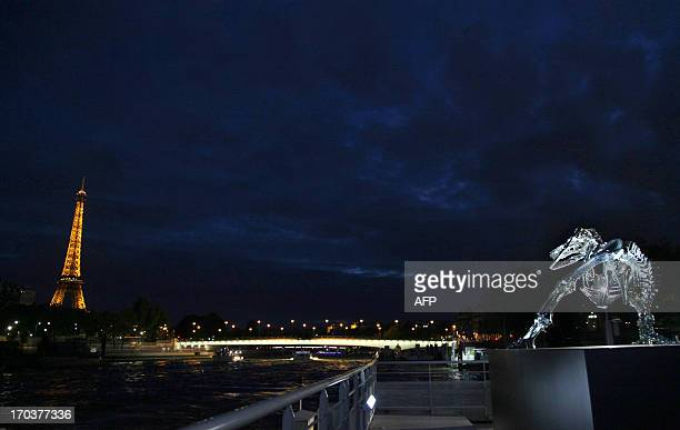 A giant chrome brushed aluminium skeleton of a Tyrannosaurus dinosaur made by French sculptor and painter Philippe Pasqua stands at the pier of...