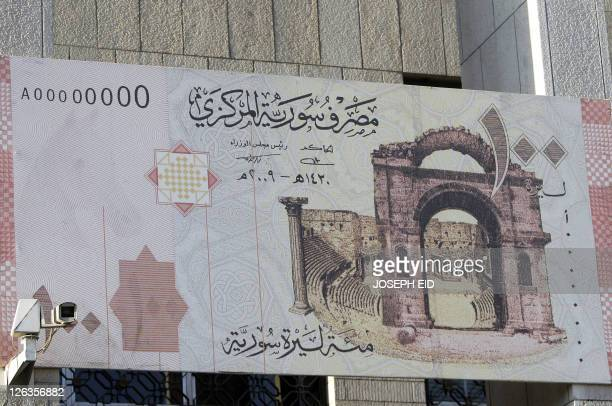 A giant copy of the new 100 Syrian lira note hangs at the entrance of Syria's Central Bank in Damascus on August 23 2011 The Syrian economy hit hard...