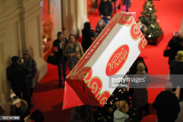 A giant display model box of 'Stolichnye' candy from the Red October chocolate factory hangs above shoppers at the GUM department store in Moscow...