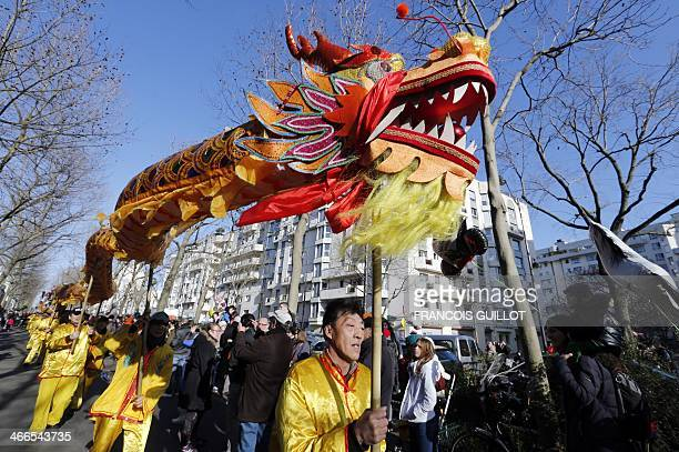 A giant dragoon is carried during a parade in a street of the Belleville district to celebrate the Chinese Lunar New Year on February 2 2014 in Paris...