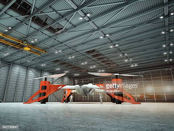 Giant drone in hangar with technicians