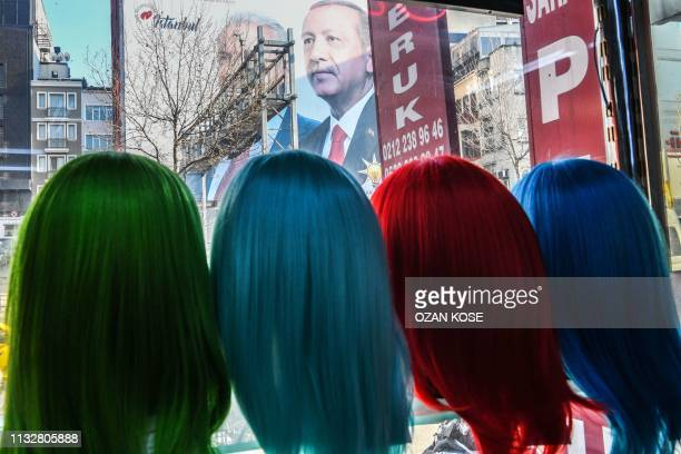 TOPSHOT A giant election poster of the Turkish President covering the facade of a building is seen from a shop's window where wig models are...