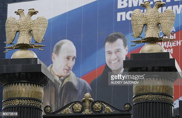 Giant election poster with portraits of Russian President Vladimir Putin and his likely successor Dmitry Medvedev sits behind two golden...
