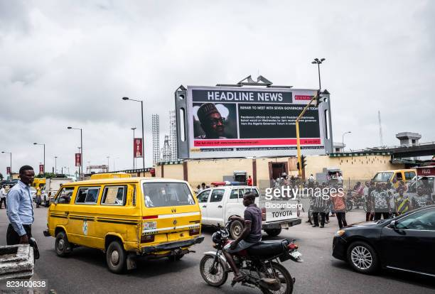 A giant electronic advertising screen displays headline news about Muhammadu Buhari Nigeria's president to pedestrians in Lagos Nigeria on Wednesday...