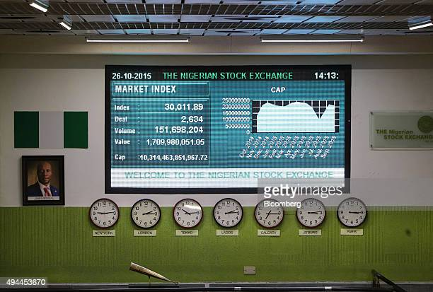 A giant electronic screen displays market data above global time zone clocks on the trading floor at the Nigerian Stock Exchange in Lagos Nigeria on...