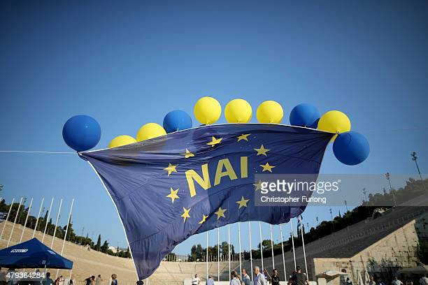 A giant European Union flag emblazoned with the greek word 'Nai' flys above the Olympic stadium as supporters ofthe 'Yes' campaign attend a rally and...