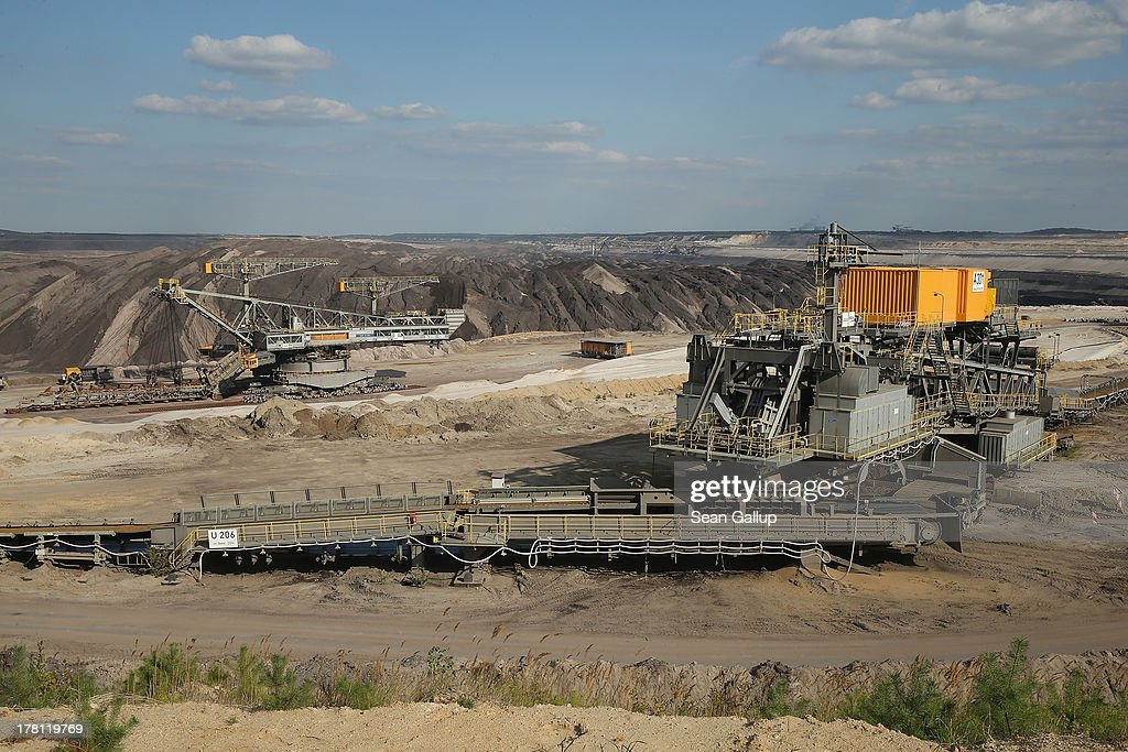 A giant excavator (L) and a conveyor belt system ferrying topsoil stand at the Welzow Sued open-pit lignite coal mine on August 26, 2013 near Welzow, Germany. Welzow Sued, operated by Vattenfall, is among the last active open-pit mines in a region known as the Lausitzer Seenland, where dozens of former mines have been turned into lakes. In a development project initiated by state government, other nearby former open-pit mines that once evoked a lunar landscape are being turned into lakes in a long-term rejuvenation effort that is also intended to make the area a viable tourist destination. Mineral residue in the mines, however, is proving a difficult stumbling block that is making many of the new lakes too acidic to sustain marine life in the short term.