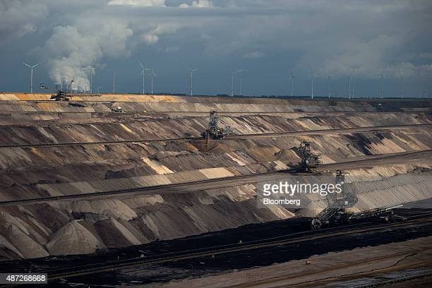 A giant excavator and mining machinery operate at an open pit lignite mine also known as brown coal operated by RWE AG in Hambach Germany on Monday 7...