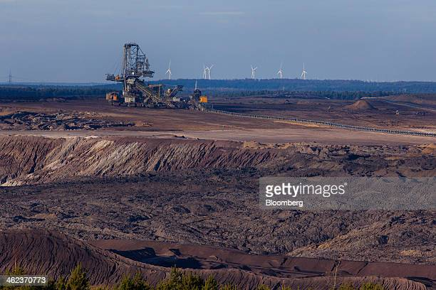 A giant excavator collects lignite also known as brown coal from the openpit mine operated by Vattenfall AB as wind turbines stand on the horizon in...