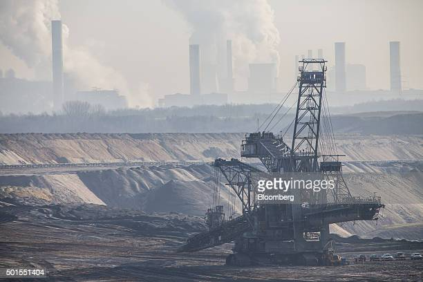 A giant excavator operates at the Garzweiler open cast lignite mine operated by RWE AG as chimneys emit vapor at a power plant beyond in Garzweiler...