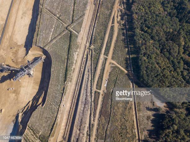 A giant excavator operates at the open pit lignite mine operated by RWE AG as trees stand in the Hambach forest in Hambach Germany on Friday Oct 5...