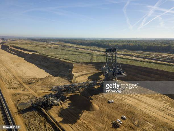 A giant excavator operates at the open pit lignite mine operated by RWE AG as trees stand beyond in the Hambach forest in Hambach Germany on Friday...