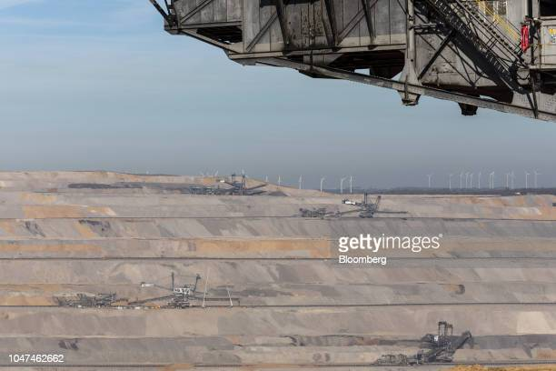 Giant excavators operate at the open pit lignite mine operated by RWE AG as wind turbines stand beyond in Hambach Germany on Friday Oct 5 2018 The...