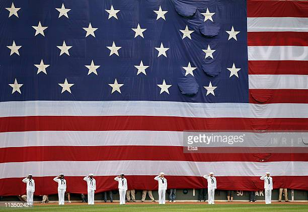 A giant flag covers the Green Monster as the national anthem is played before the game between the Boston Red Sox and the Los Angeles Angels on May 2...