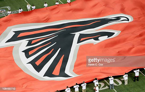 A giant flag with the Atlanta Falcons logo is seen on the field against the Green Bay Packers during their 2011 NFC divisional playoff game at...