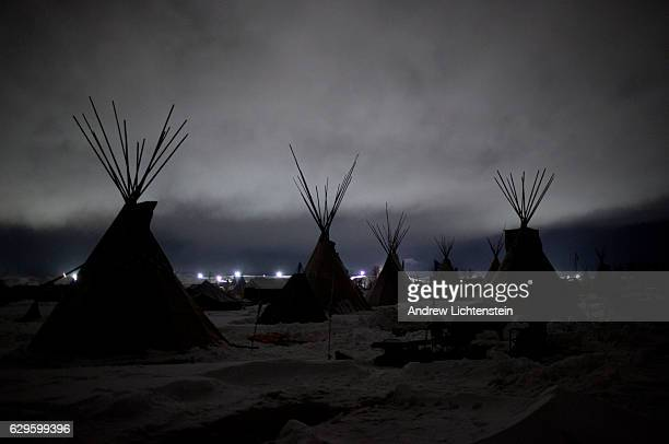 Giant flood lights set up by a popeline company and law enforcement illuminate a cloudy winter night at the Oceti Sakowin camp Just outside of the...