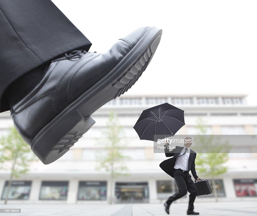 giant foot stepping on male executive : Stock Photo