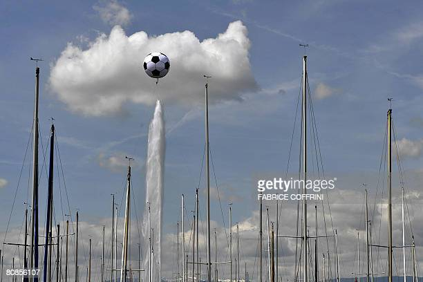 A giant football is seen floating above the Geneva's fountain behind sailing boat's mats on April 25 2008 in the Geneva harbour The helium inflated...