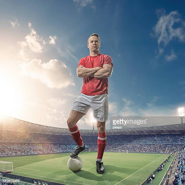 Giant Footballer Standing in Floodlit Soccer Stadium At Sunset