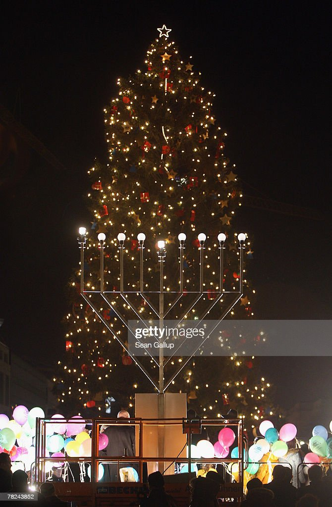 Jews Christmas Trees.A Giant Gas Lit Menorah Stands In Front Of A Christmas Tree