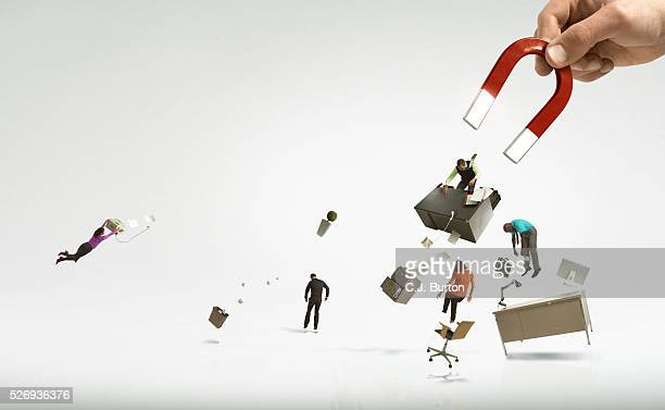 giant hand and magnet picking up office and workers - downsizing unemployment stock pictures, royalty-free photos & images