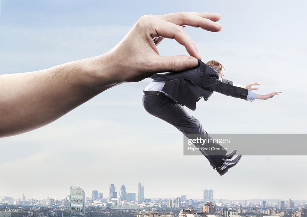 Giant hand lifting up a business man in the city : Stock Photo